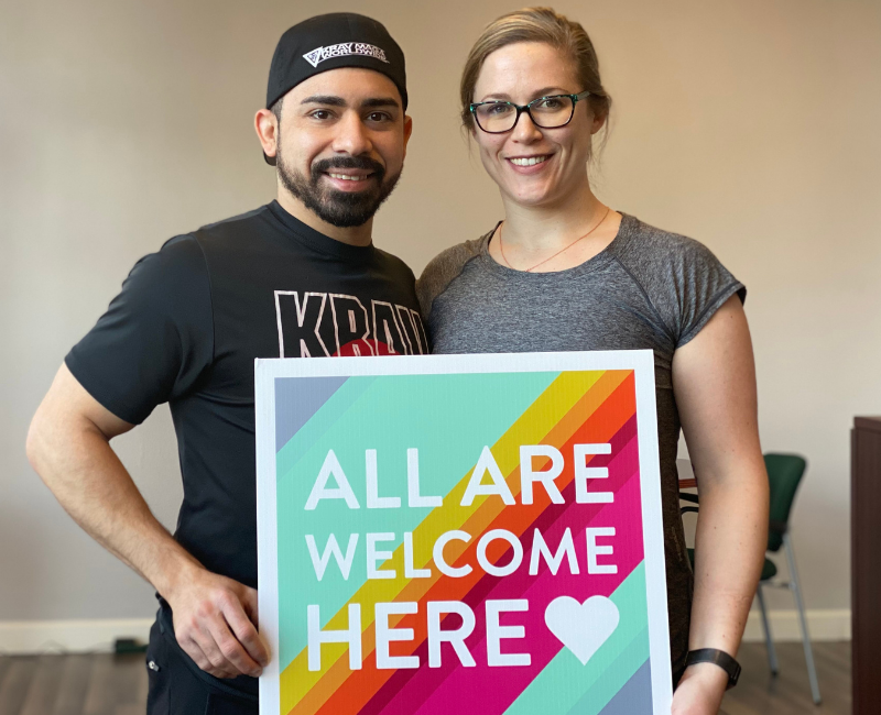 "Omar and Margaret, owners, hold a sign saying ""All Are Welcome Here"""